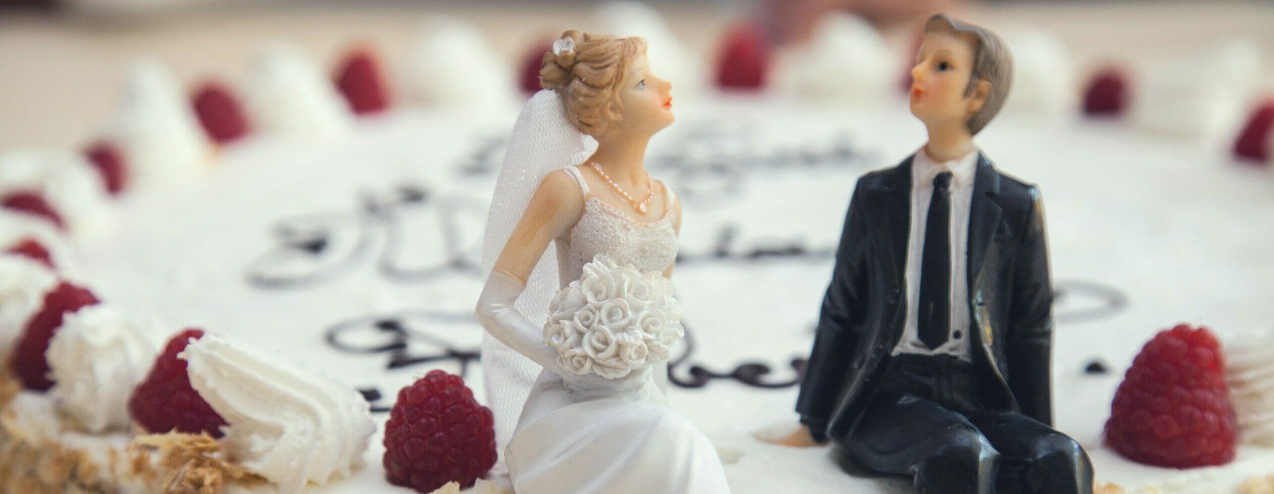figurki pary młodej siedzącej na torcie